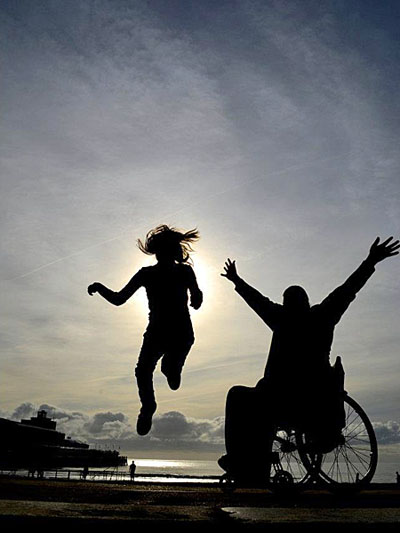 figure in wheelchair with arms in air anda second figure leaping into air